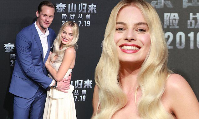 A beaming Margot Robbie and Alexander Skarsgard cuddle up on The Legend Of Tarzan red carpet.