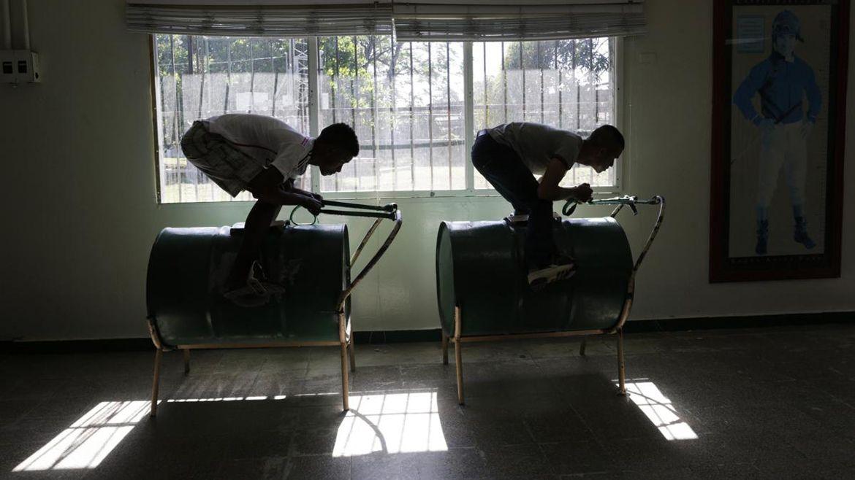 Aprendices de jinete practican la posición de carrera en el barril