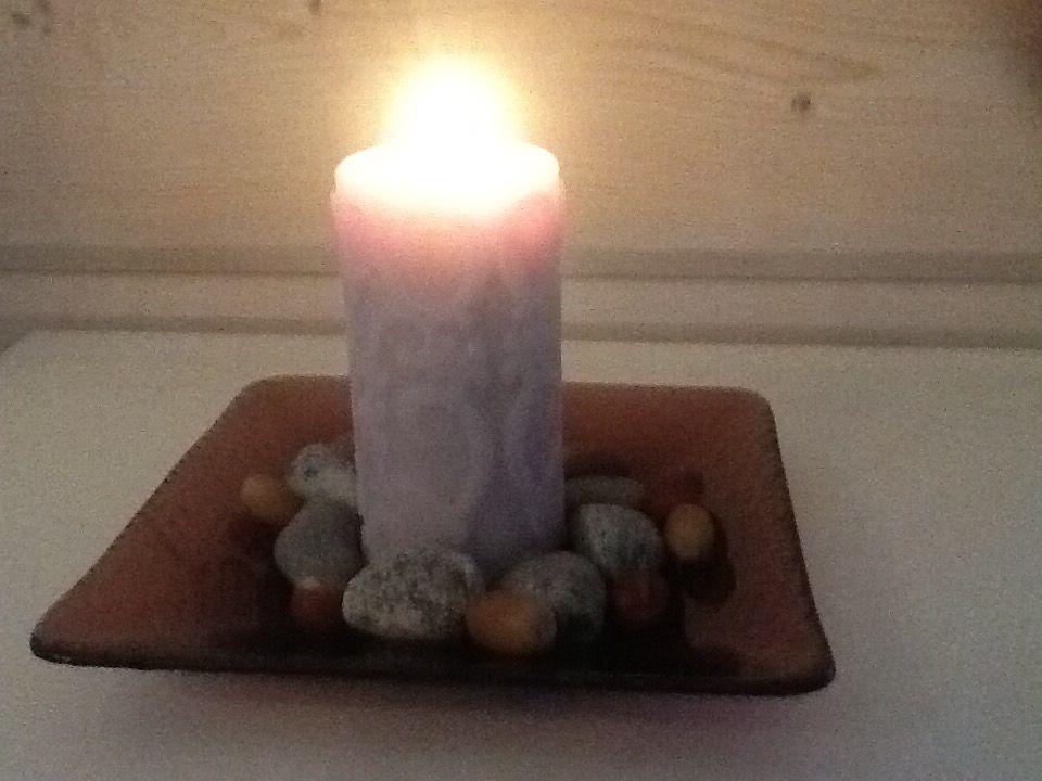 Kynttilä ja kiviä.