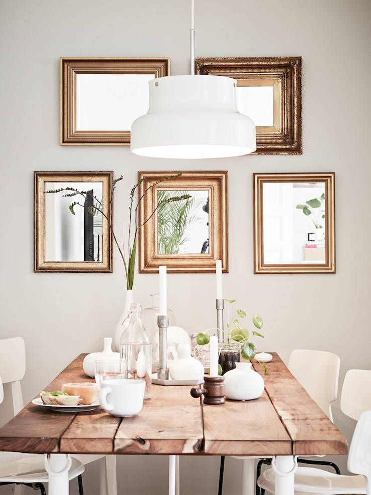 golden mirrors + the rustic wooden table adds warmth to this modern dining room