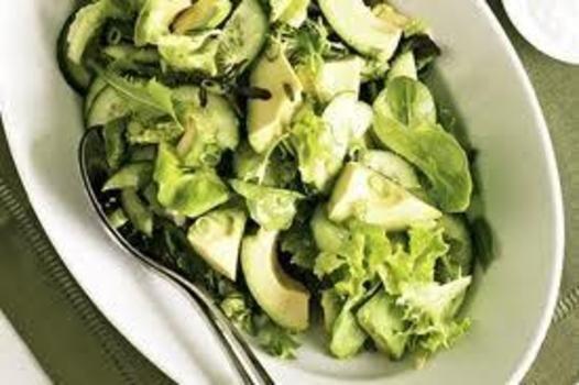 Bland salatbladene, hakket avokado, løk og agurk i en bolle. Hell sitronsaft og olje i en krukke med skrulokk. Tilsett salt.