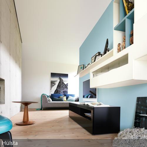 Die hellblaue Wandfarbe lässt den kleinen Raum größer wirken, während der türkisfarbene Sessel und die natürlichen Holzdielen für Gemütlichkeit sorgen.…
