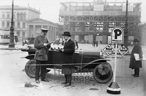 Ein Autofahrer entrichtet seine Parkgebühr in Berlin. Das Schild der Wachgesellschaft weist auch auf eine Tankstelle und eine Werkstatt hin.