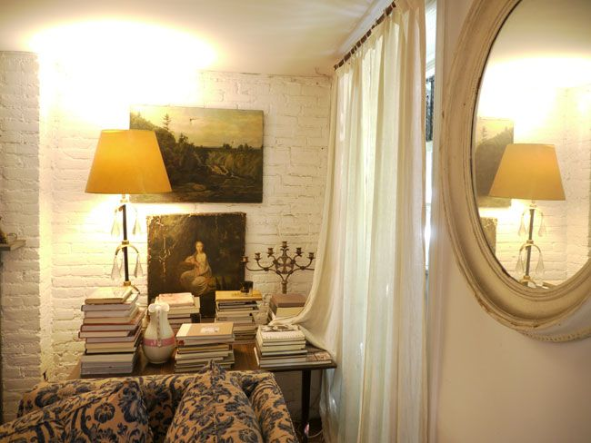 oval mirror, old painting, white brick interior wall, white curtains ...