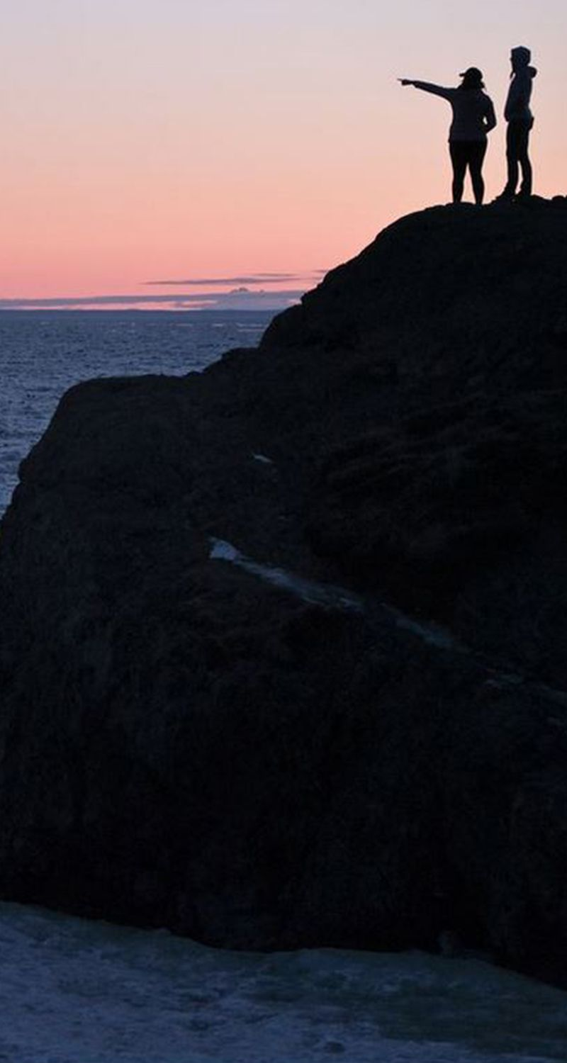 After sunset, two people take in the view from a rocky overlook. A crowed gathered at Beluga Point on Turnagain Arm to watch the sunset and take in the icy view on March 26, 2017. (Marc Lester / Alaska Dispatch News)
