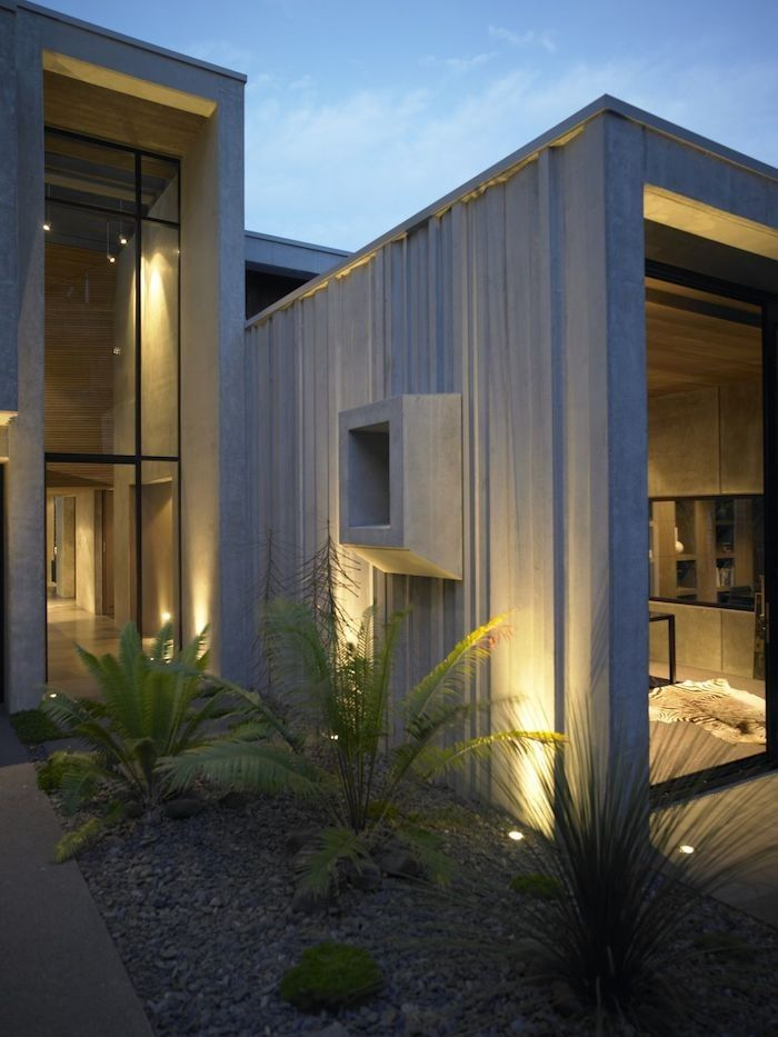 Uplights highlight the ribbed concrete architectural detail while providing ambient lighting and a visual path to the entry of the karaka bay house in