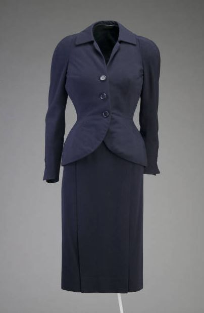 "Suit, Christian Dior, Paris, France: 1951, silk-lined wool. ""Christian Dior often repeated successful themes or designs from his couture lines for the Dior-New York ready-to-wear styles the following season. Another suit in the Chicago History Museum's collection, object number 1977.127.3a-e, illustrates this process. This suit is a couture original while the suit inspired by it was designed for the New York ready-to-wear salon and cost a fraction of the couture price."""