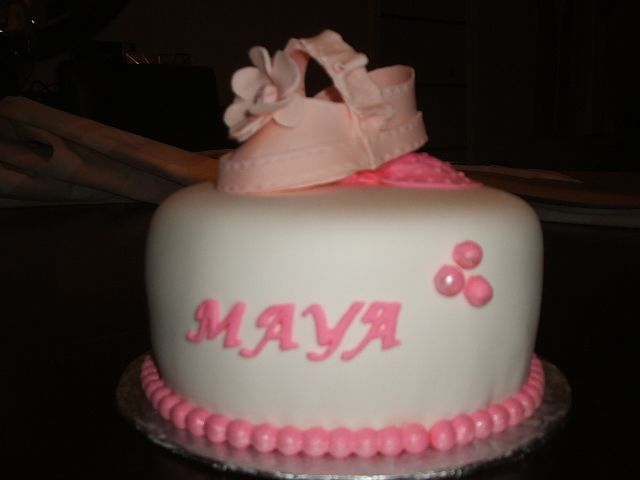 One tier unique white and pink fondant baptism cake with pink fondant baby shoe. Everything on this cake is edible, it's a 3 layer red velvet with cream cheese.
