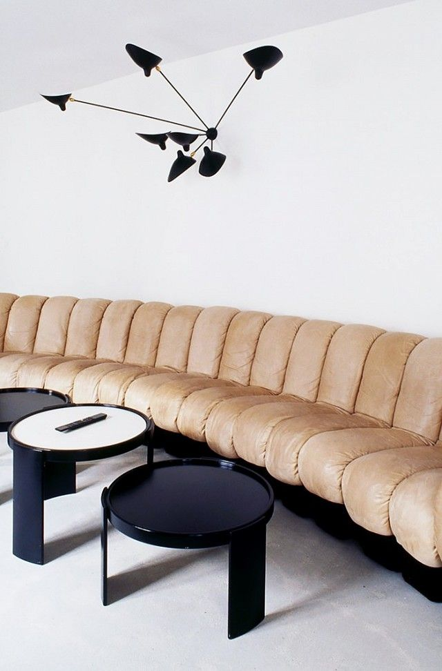 Living Room With A Neutral Tufted Sofa, And A Modern Black Wall Sconce