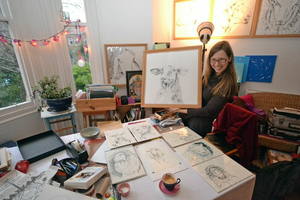 Birgit Deubner in her studio, looking through some drawings with a client.