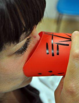 Vaso de plástico recortado por uno de los lados para poder introducir la nariz y/o las gafas sin necesidad de elevar la cabeza.  Ana Caridad Cerezo Guillén
