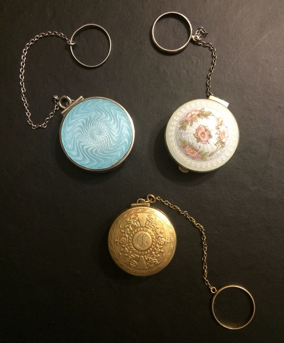 Tango or Finger Ring Compacts. No case identification on any of the three. Sterling Silver & blue enamel. Flip side has initials engraved on it. Sterling Silver mark on the inside lid. Sterling silver White enable with floral design. 14K gold, dual opening with an initial on one side.