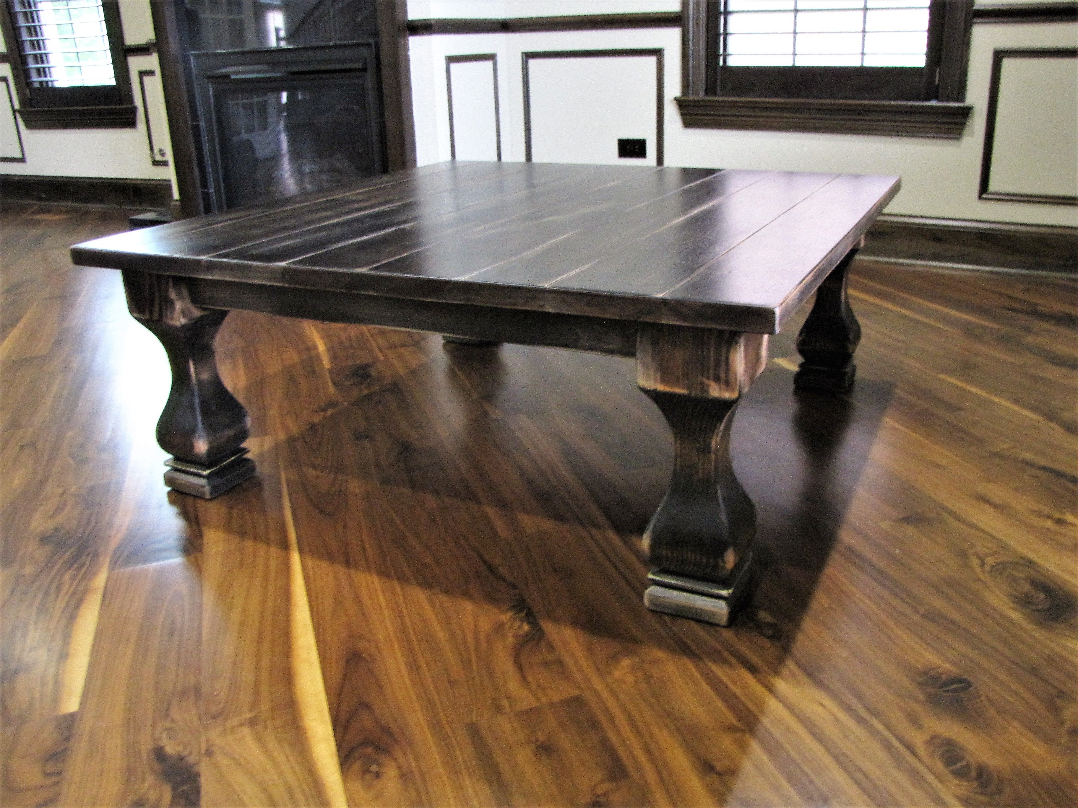 Dark belly pedestal coffee table with scuffing giving the table a