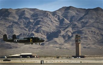 A North American B-25J Mitchell takes flight during the open house at Nellis Air Force Base, Nev., Nov. 9, 2014. The B-25 was one of the most heavily armed airplanes in the world and was used for high- and low-level bombing, strafing, photo-reconnaissance, submarine patrol, as a fighter, and was distinguished as the aircraft that completed the historic raid over Tokyo in 1942. (U.S. Air Force photo by Airman 1st Class Rachel Loftis)
