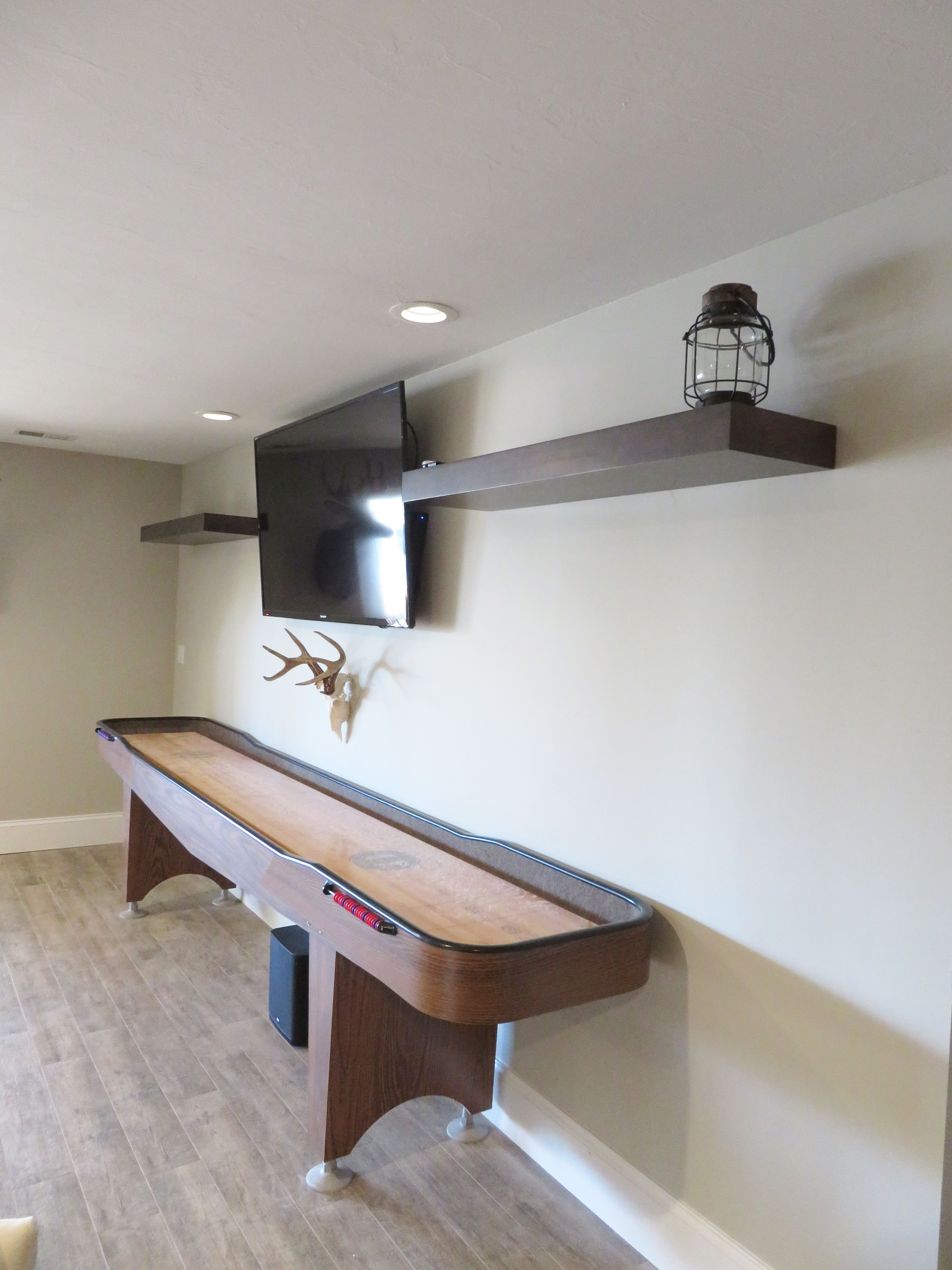 Decorative Floating Shelves In A Game Room By Woodland Cabinetry