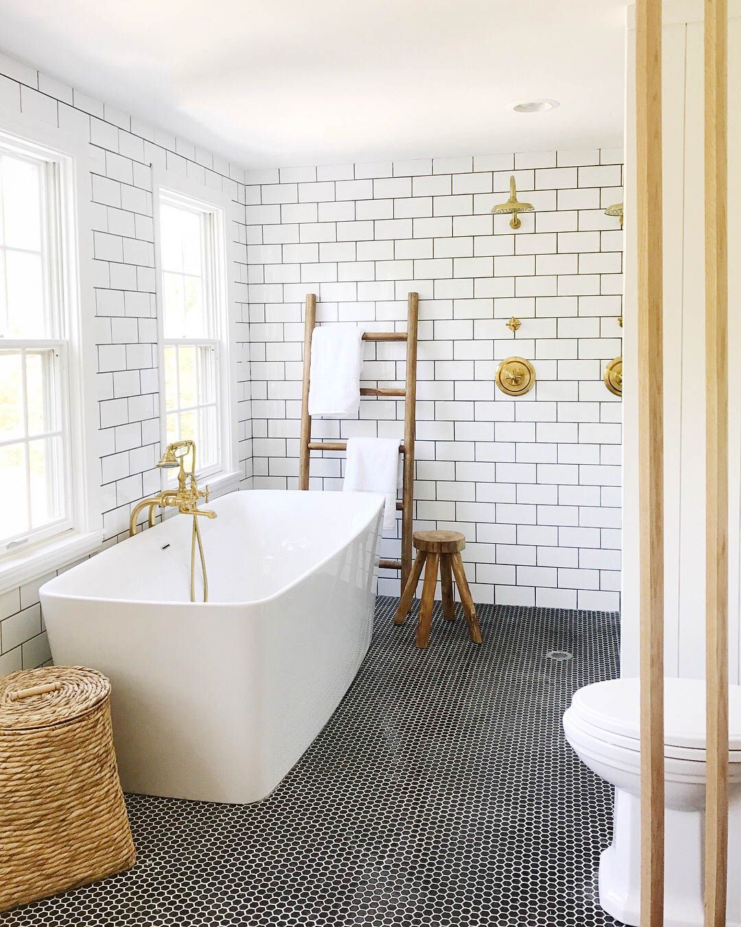 White Subway tile bathroom with brass and black hex tile floor ...