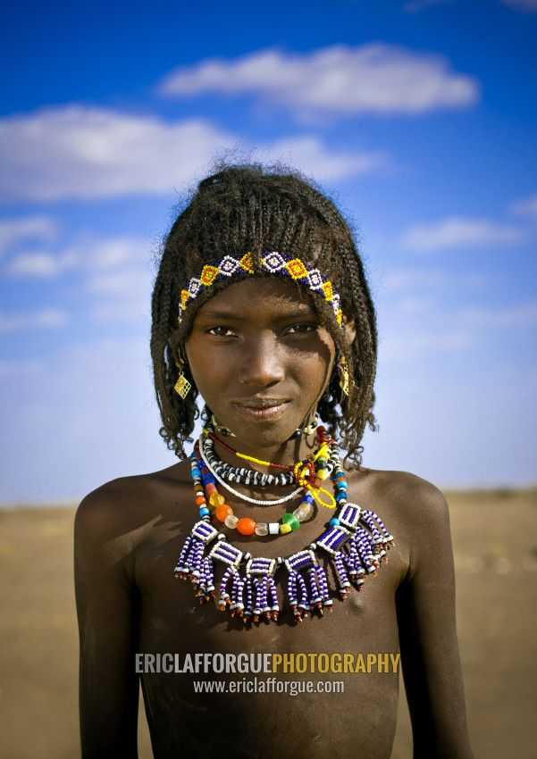 Portrait of a smiling Afar tribe girl with braided hair an