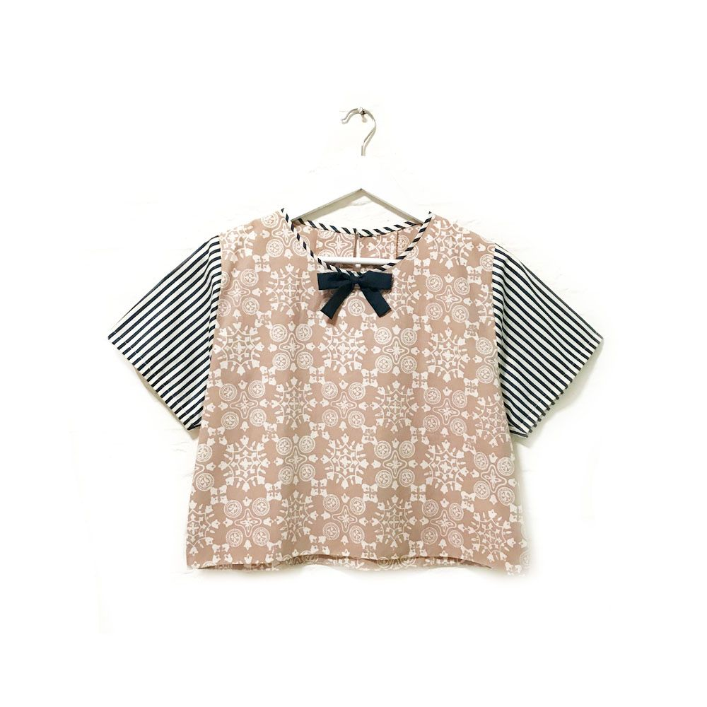 Anna 003  IDR 315.000  Casual Loose Fit Hand Stamped Batik Blouse with Bow Tie and Stripe Pattern Combination  Length of Blouse : approx. 48 cm  Material Used : Hand Stamped Batik, Cotton / Navy Blue Bow Tie / Stripe Pattern Fabric, Cotton  Note: one button at the back for opening