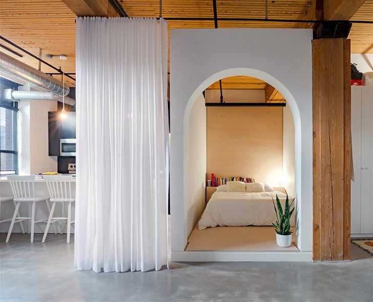 Brick walls and bedroom behind the curtain unusual loft in Toronto