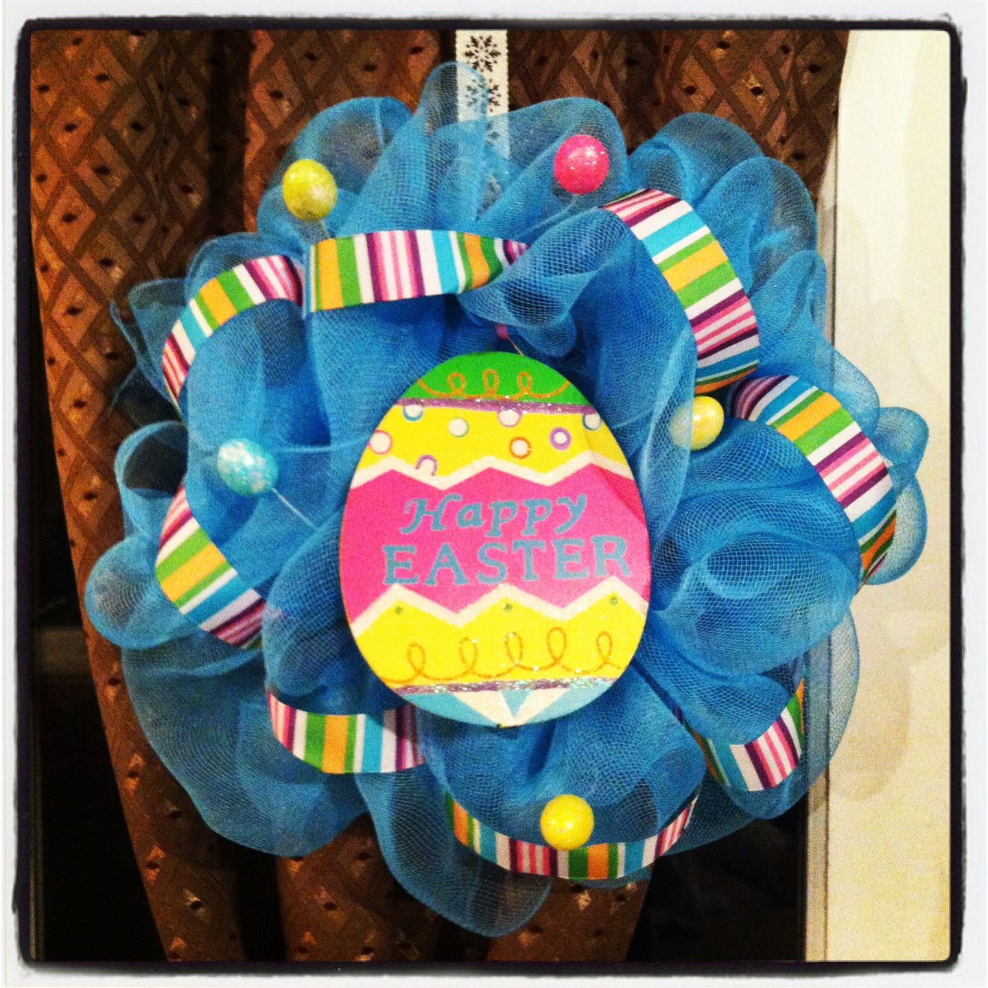 Fascinating Blue Mesh Easter Wreath Idea with Crafted Paper Egg and Colorful Stripes Ribbons and Mini Plastic Eggs
