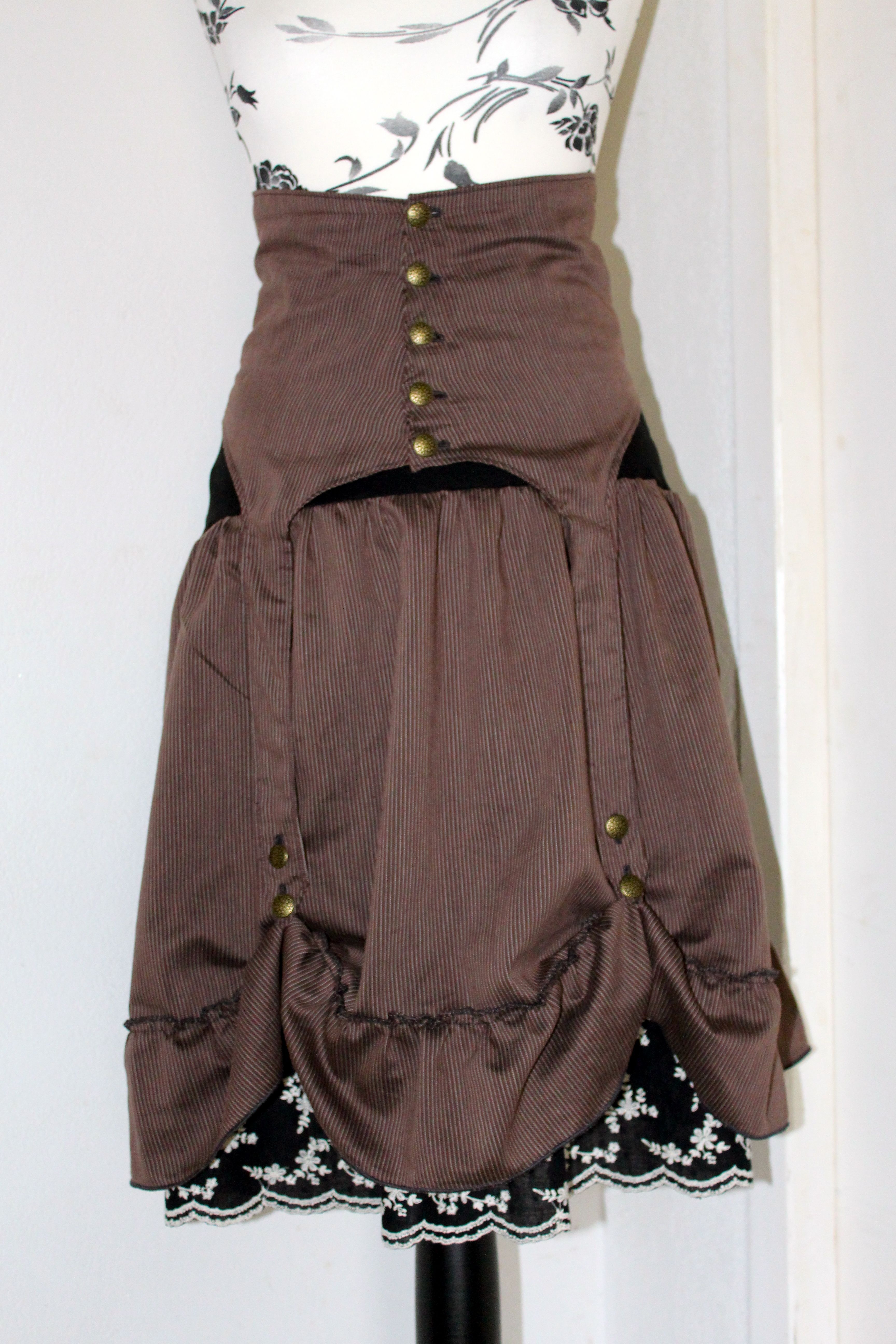 Ensemble steampunk jupe marron rayé avec son serre taille porte jarretelle qui laisse découvrir un jupon noir brodé de petites fleurs blanche sous la jupe. Création de Noeden/facebook