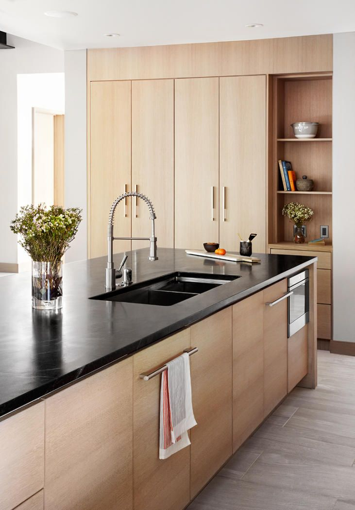 A wooden kitchen with a black countertop is featured in
