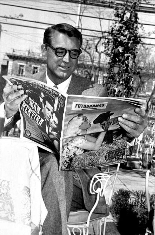 Cary Grant reading a Fotogramas magazine while in Spain filming 'The Pride and the Passion', c. 1950's. ☚