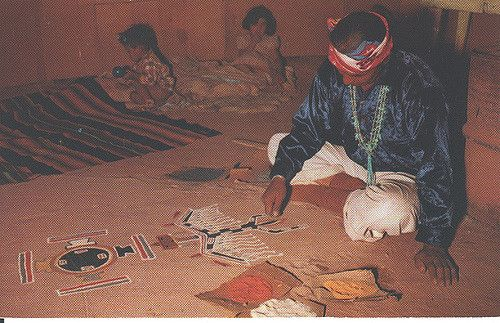 """Vintage Postcard of Navajo Sand Painter - Joe Lee Lukachukai. Are these his children in the background? Or someone in need of this ceremony? Probably, the photographer has staged this photo. But, back reads"""" """"Joe Lee Lukachukai carefully executing a painting in sand to invoke the Great Good Spirit to bring health to the sick"""""""
