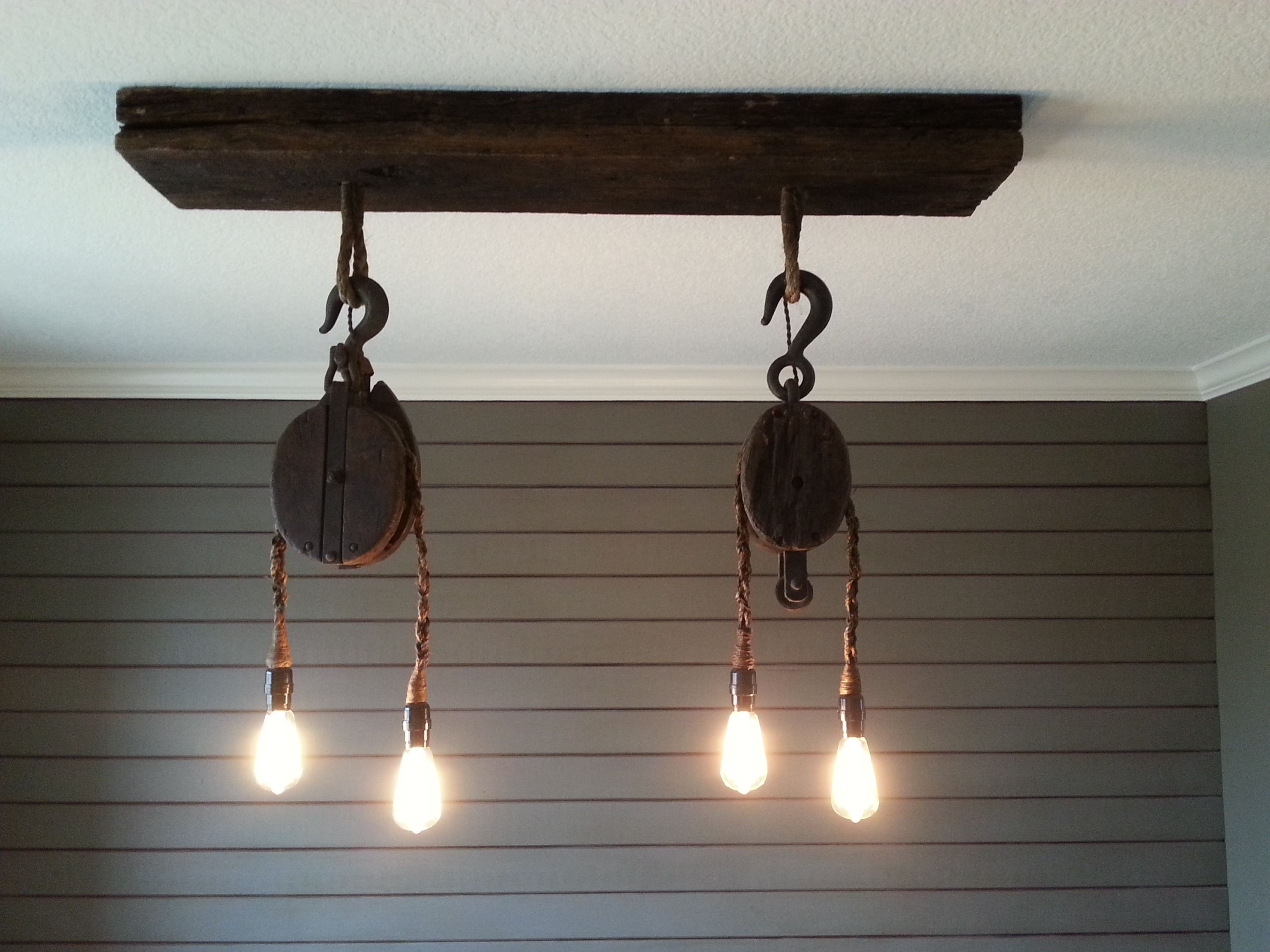 Custom light fixture from vintage pulleys.  Ceiling plate from reclaimed wood. www.facebook.com/thetealbutterfly