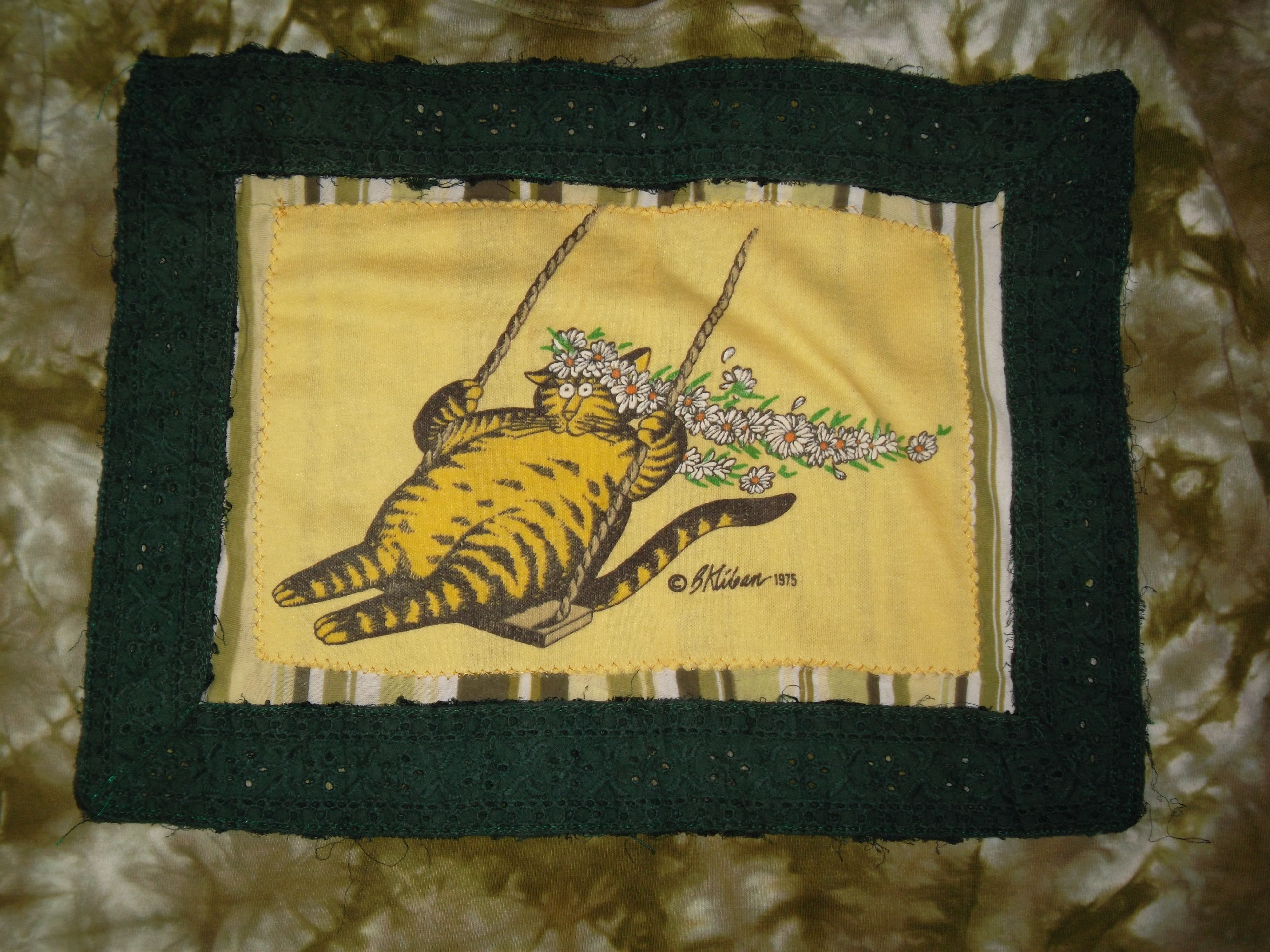 Detail: Kliban's Cat on a Swing, framed with eyelet lace and stitched to a tie-dyed shirt.