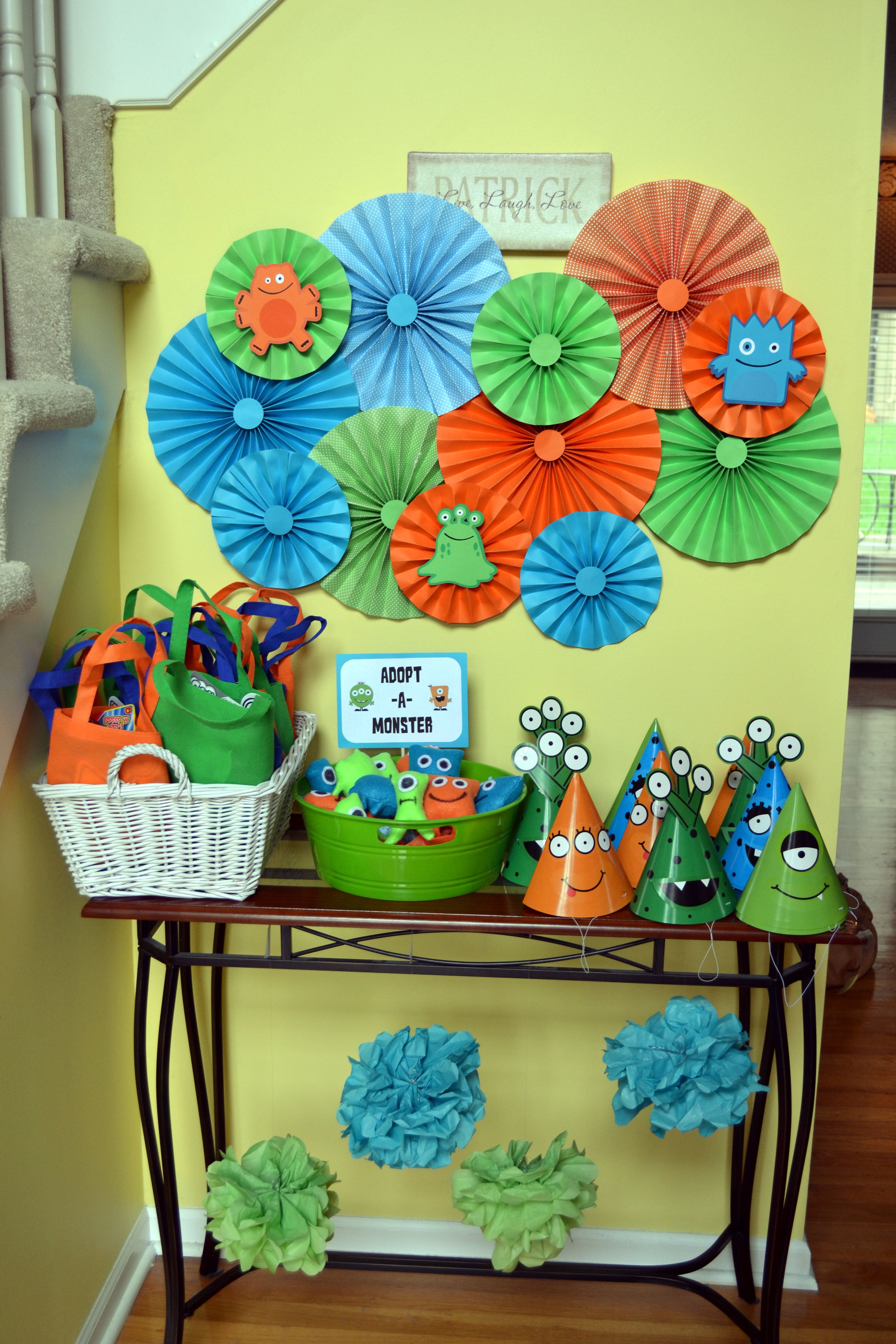 DIY Paper Medallions decorate the nook where the favor bags and party hats were #monster #birthday