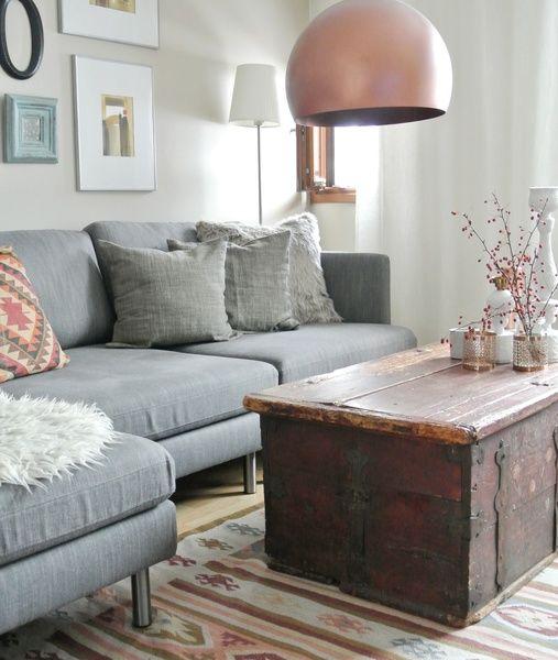 harmaa sohva,kelim matto,kuparivalaisin,arkkupöytä,tauluseinä