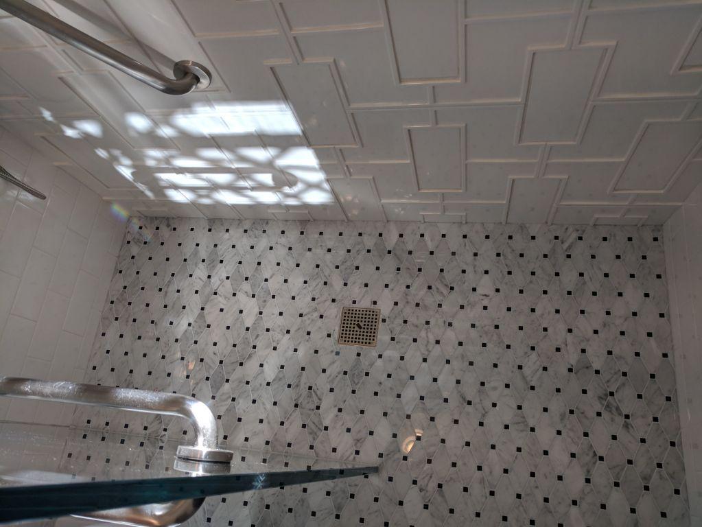 Carrara mosaic on the floor – ceramic tile on the wall
