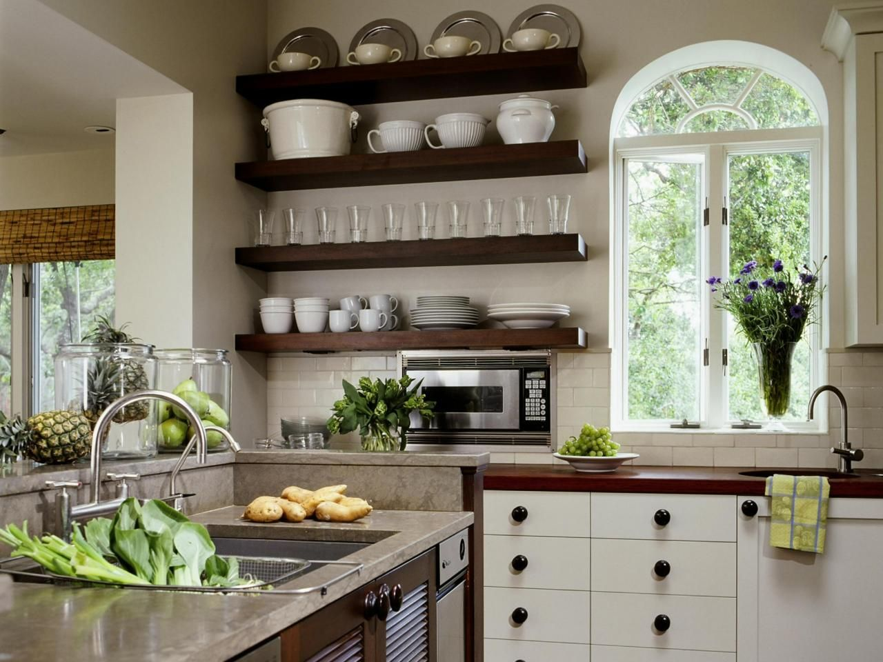 Floating shelves used to store dishes and a large window Floating shelf ideas for kitchen