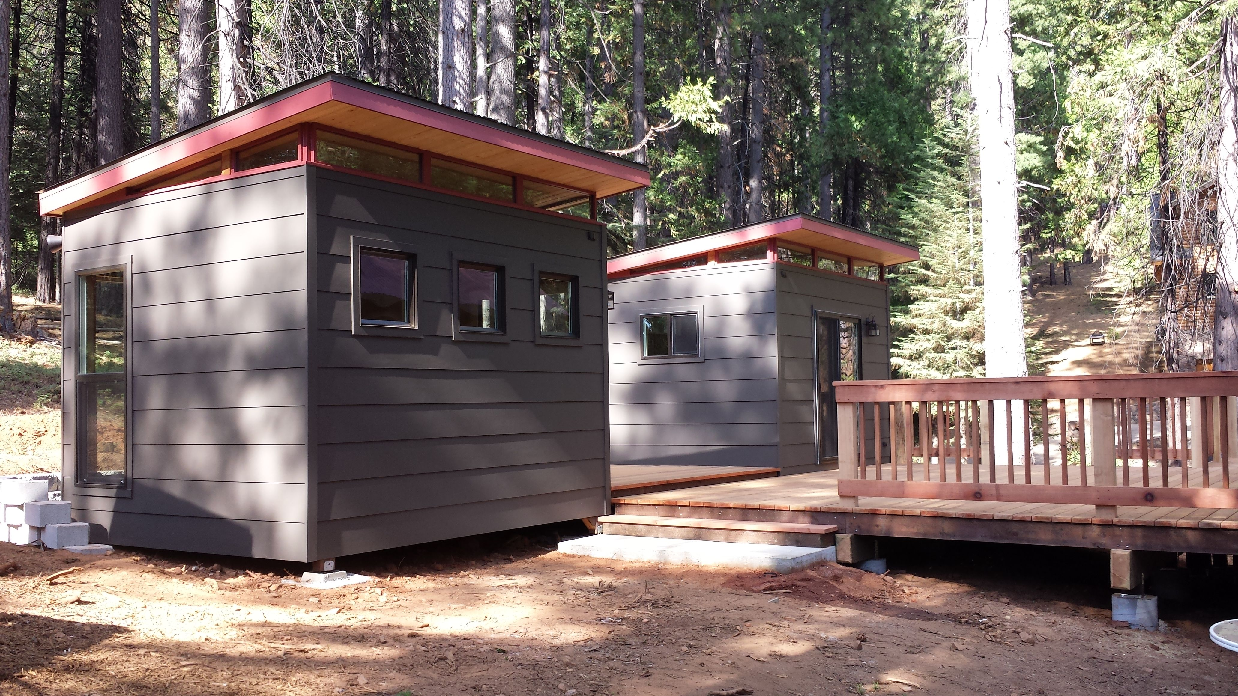 The two sheds are connected to a cabin via a custom deck.