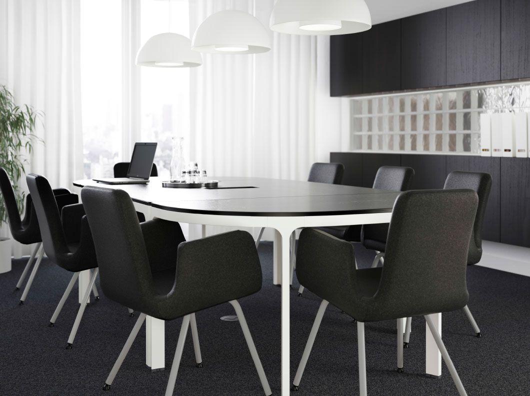 Grande sala riunioni con tavolo marrone nero con gambe bianche e