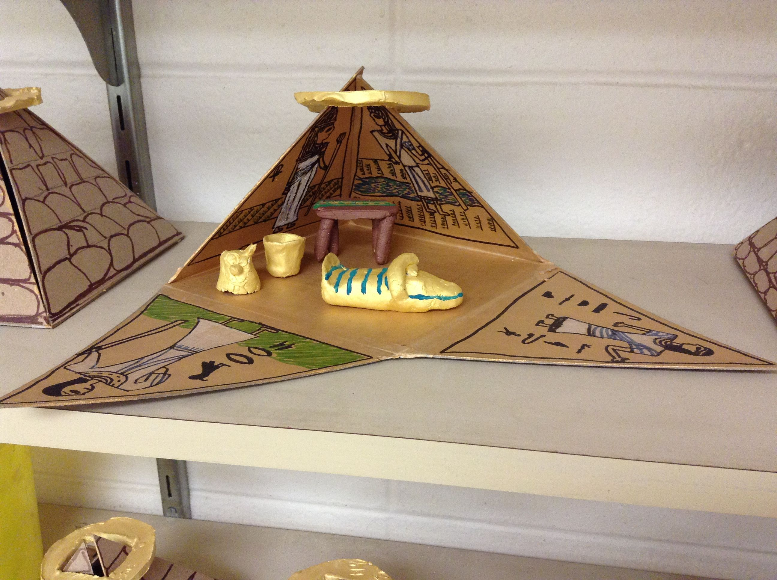 Pyramids with fold away sides and clay coffins and other pieces. (Ka)