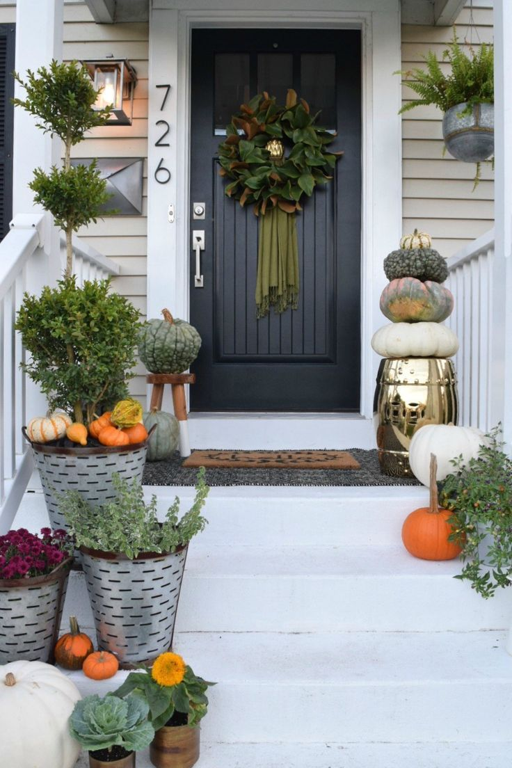 Fall front porch decor with rich colors and all the pumpkins! #falldecor #pumpkins #frontporch #porchdecor #exteriors