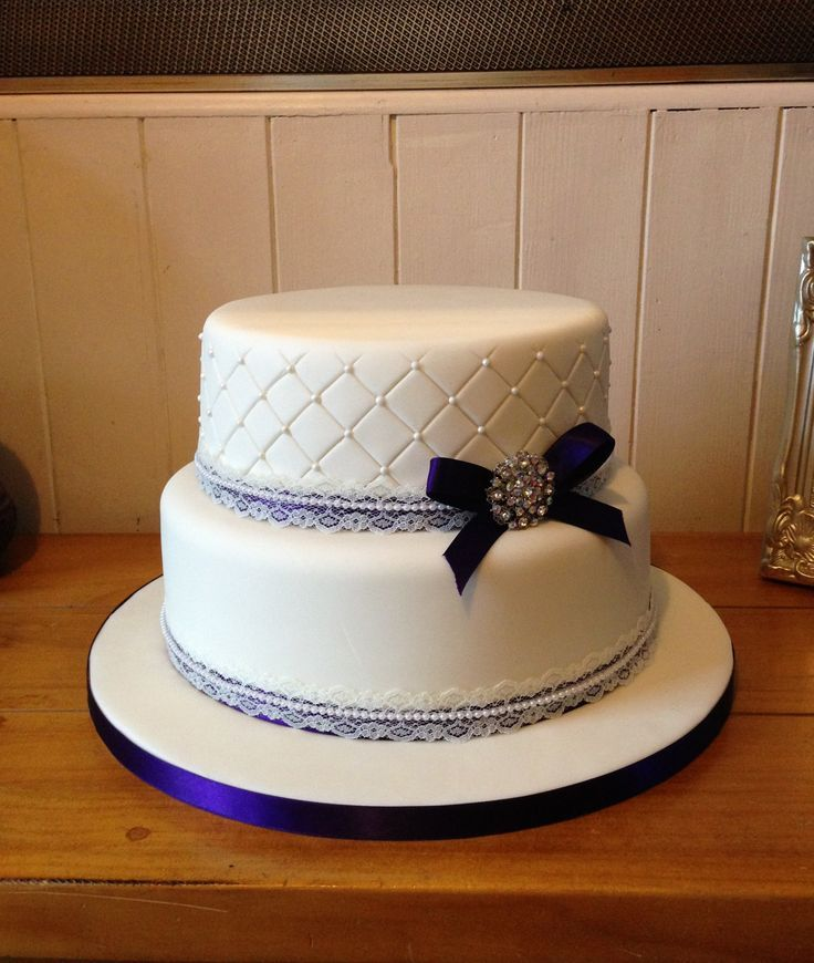 2 Tier Ivory Wedding Cake With Quilted Top Embossed Sugar Pearls Is Finished A Purple Satin Ribbon An Lace And Vintage