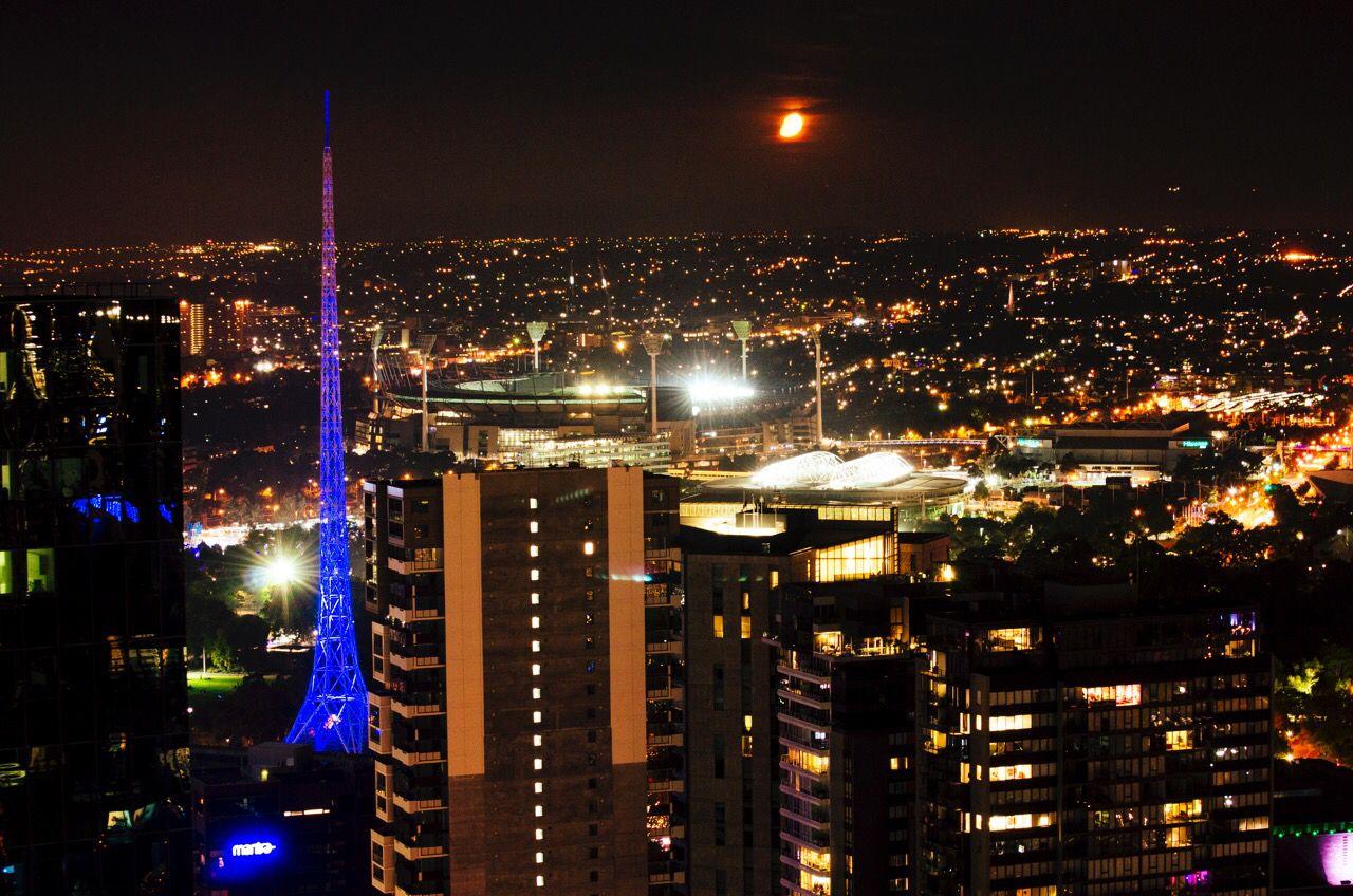 Long exposure photography capturing the Star Wars like orange moon over Melbourne CBD. Arts Centre precinct with blue lighting