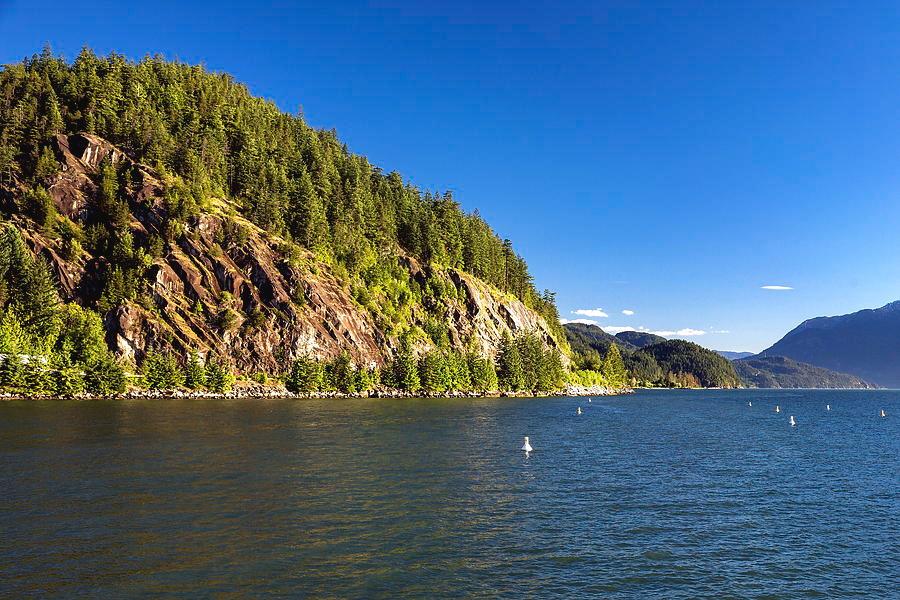 North America Photograph - A Cliff Over The Sea by Alex Lyubar #AlexLyubarFineArtPhotography #VancouverCanada#StraitOfGeorgia#SunnyDay#Seascape#Cliff#RockyIsland#BlueSky#ArtForHome #FineArtPrint#ArtPrintForSale