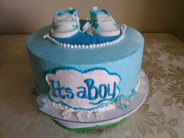 Two tier whip cream baby shower cake with elephant holding a blanket