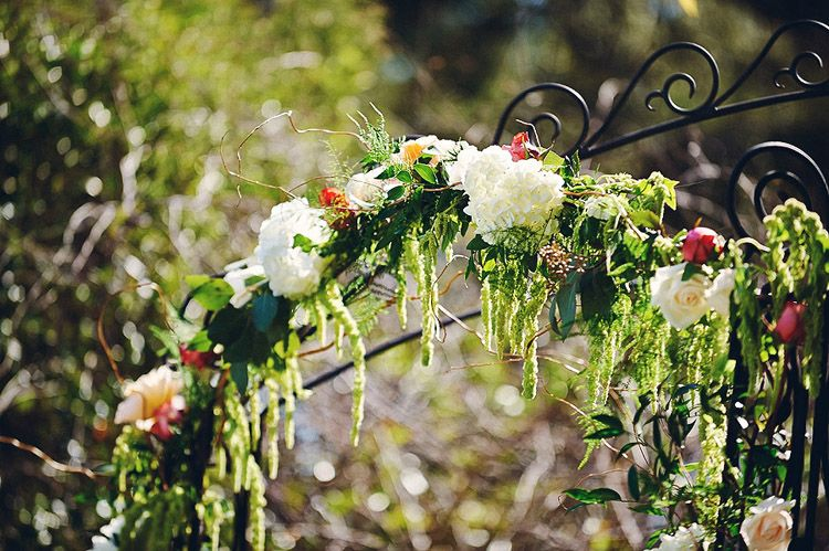 Gorgeous flower arbor with white hydrangea, flowing greenery, hanging amaranthus and soft peach tones.  The perfect spring wedding at Watercolor, Florida.  Design by Bella Flora 30a.  Photography by Paul Johnson.
