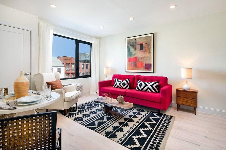 rotes Sofa mit schwarz-weißen Kissen und ähnlichem Teppich - wohnzimmer ideen rote couch
