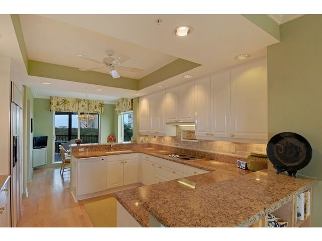 Tropical coastal green kitchen in Naples, Florida - white cabinets.  Toscana at Bay Colony | Naples, Florida
