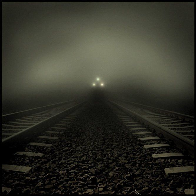 Beware what lurks upon trains and their tracks.  Train approaching out of dark fog...photographer unknown