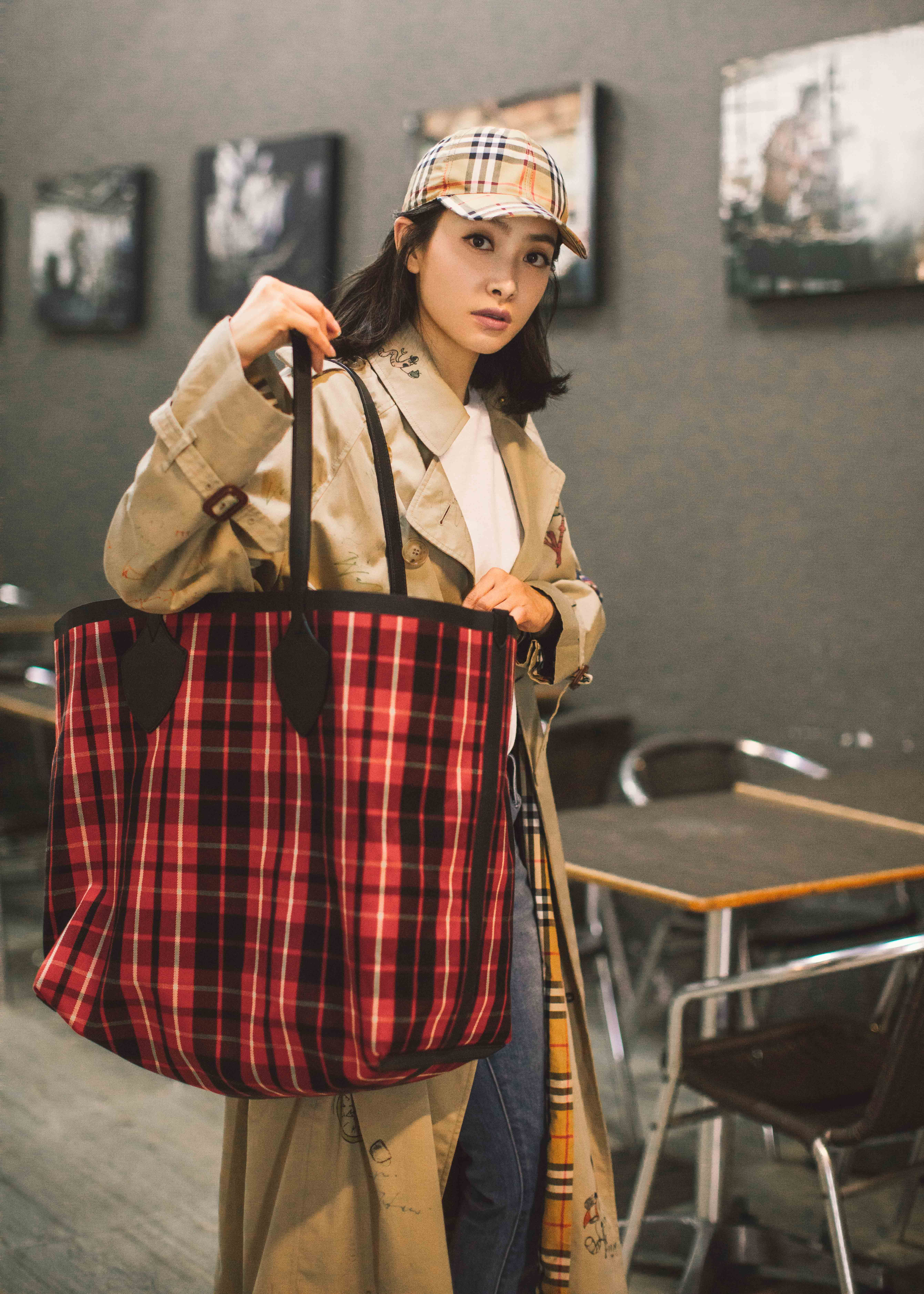 Singer victoria song wears the new burberry sketch print trench coat styled with the giant tote and a vintage check cap in thailand