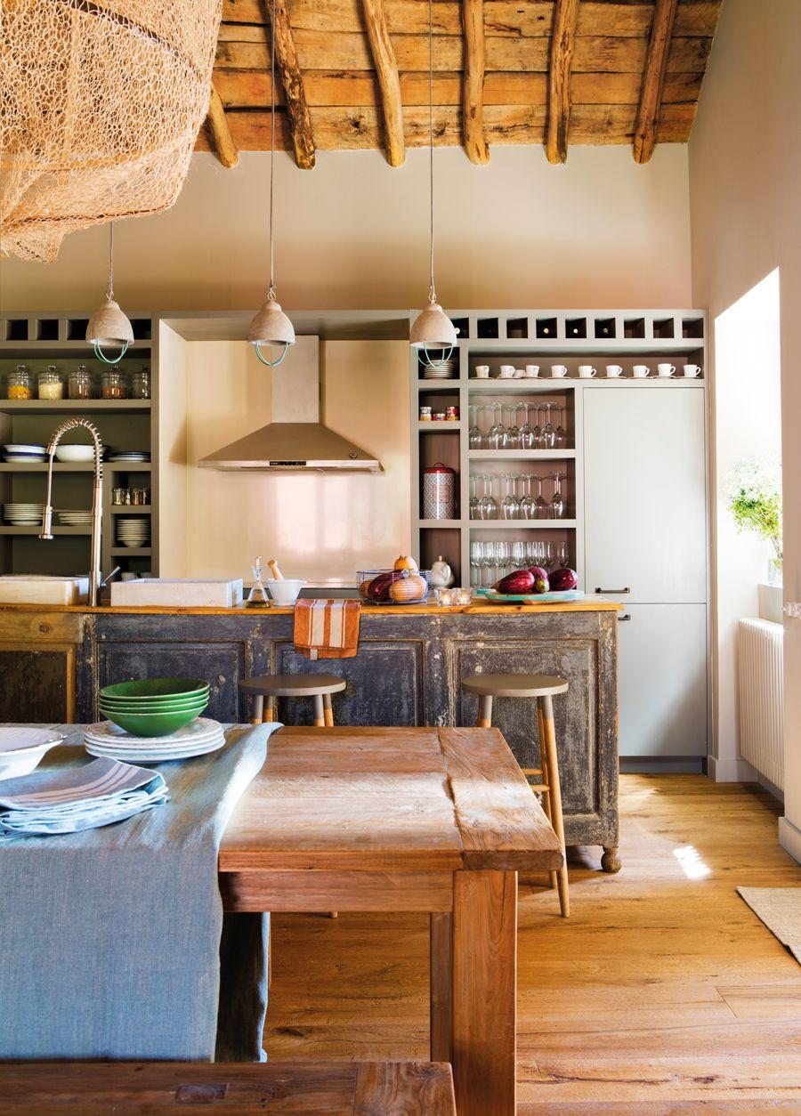 Cocina rústica abierta a comedor con mesa y bancos de madera y ...