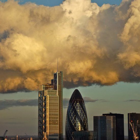 White cloud spreads across blue sky above London's Gherkin and other tall buildings