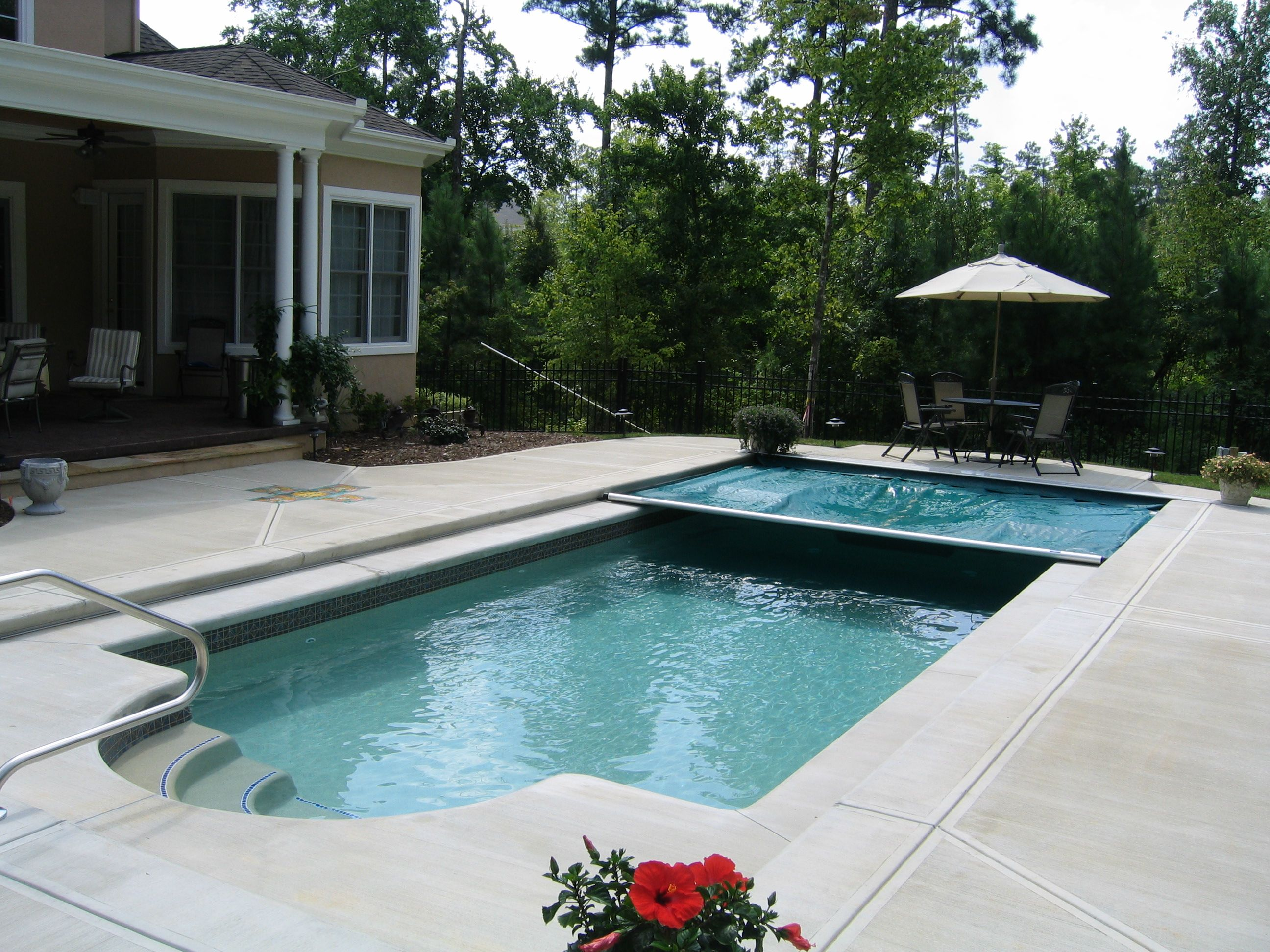 Fiberglass inground pool with pool cover partially unfurled